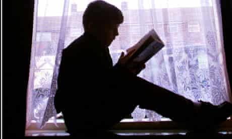 An anonymous boy sitting by the window