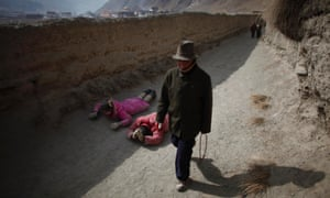 An ethnic Tibetan couple prostrate and pray during the Tibetan new year at the Labrang monastery in Xiahe county, Gansu province, China