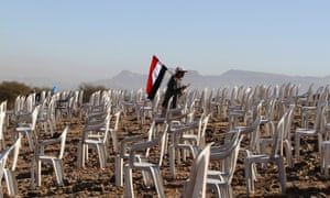 A tribesman carries a Yemeni national flag as he walks between chairs before a rally to commemorate the second anniversary of the uprising against former president Ali Abdullah Saleh in Bani Hushaish, north of the capital Sana'a