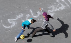 Egyptian boys play soccer in Tahrir Square, the focal point of the Egyptian uprising, in Cairo this morning. The Arabic on the ground reads: 'Morsi step down.'