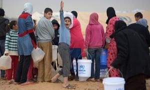 Syrian refugees fetch water at Zaatari refugee camp in Jordan.