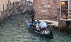 People getting drenched in a gondola in a small canal behind St Mark's Square during heavy sleet in Venice today.