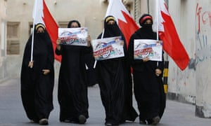 Anti-government protesters hold Bahraini flags and signs saying 'We will return till Judgment Day', as they participate in a protest in the village of Sanabis, west of Manama, Bahrain.