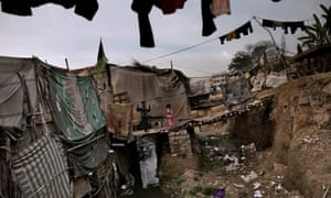 A Pakistani boy and his sister stand outside their home on a wooden bridge over sewage and rubbish, in a Christian neighborhood in Islamabad, Pakistan.