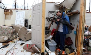 Charlie Ramp salvages guns from his tornado-damaged home in Hattiesburg, Mississippi.