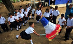Schoolchildren play with a pinata in the yard of Jean Paul Genie primary school during the year's first day of classes, in Managua, Nicaragua.