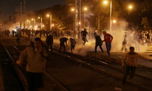 Egyptian protesters, demonstrating against Hosni Mubarak's elected successor, run for cover from tear gas fired by riot police during clashes next to the presidential palace in Cairo.