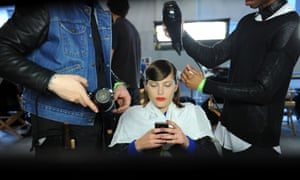 Bored? A model is prepared backstage at the Ohne Titel fall 2013 fashion show during Fashion Week in New York.
