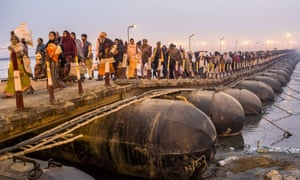 Hindu pilgrims walk across a pontoon bridge as others bathe on the banks of Sangam, the confluence of the holy rivers Ganges, Yamuna and the mythical Saraswati, during the Maha Kumbh Mela in Allahabad, India.