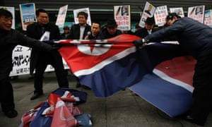 Activists from an anti-North Korea civic group try to tear a North Korea flag during a rally against North Korea's nuclear test near the U.S. embassy in central Seoul.