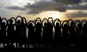 Filipino students gesture with heart symbols during a synchronized sunset viewing protest to save the Manila Bay. Members of civil society groups, advocates and students are opposing a reclamation project in the bay for a private commercial complex.