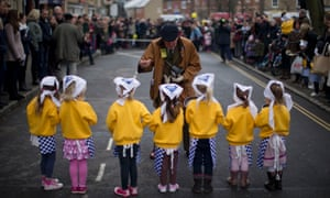 An official explains how the race works to girls from a local nursery school, lined-up ready for the start of their age group's race, during the annual Shrove Tuesday pancake race in Olney, England.