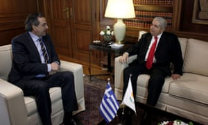 Greek prime minister Antonis Samaras and Cypriot president Demetris Christofias meet in Athens. Photograph: AFP/Getty Images/ Angelos Tzortzinis