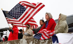 Mourners with American flags watch as the long funeral procession for slain former Navy SEAL sniper Chris Kyle travels along Interstate 35 headed for his final resting place at the Texas State Cemetery in Austin, Texas. Some 7,000 people attended a two-hour memorial service for Kyle at Cowboys Stadium in Arlington on Monday.