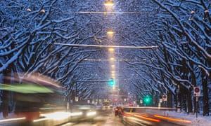 Evening traffic rolls a road beneath snow covered trees in Bern, Switzerland.