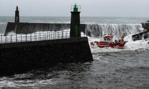 A fishing boat navigates through treacherous waves as it enters the port of Viavelez, northern Spain.