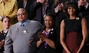 US first lady Michelle Obama stands with Cleopatra and Nathanial Pendelton, killed days after performing at the inauguration in Washigton, at the state of the union address.