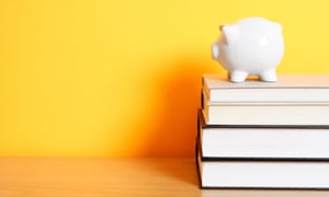 A piggy bank on top of a stack of books