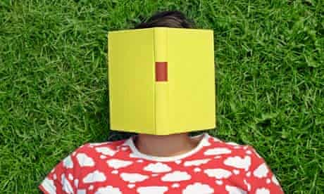 A woman lying on the grass with a book on her face