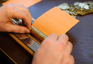 Germany's smallest bank: CEO Peter Breiter rolls euro coins in paper