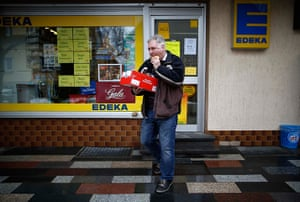 Germany's smallest bank: Peter Breiter bites into his lunchtime snack as he leaves a corner shop