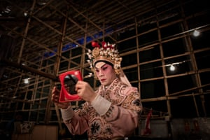 Cantonese opera: An actor applies makeup backstage in the Bamboo Theatre