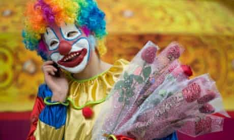 A carnation-selling clown speaks on a mobile phone at the entrance to a park in Beijing.
