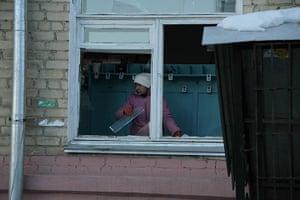 meteorites in Russia: A woman removes broken glass from a window frame in Chelyabinsk