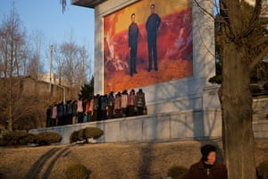 20 Photos: North Koreans before a mosaic of late leaders Kim Il Sung and Kim Jong Il