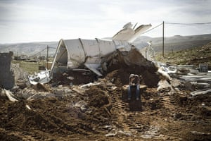 20 Photos: An Israeli settler sits praying among the rubble of his house