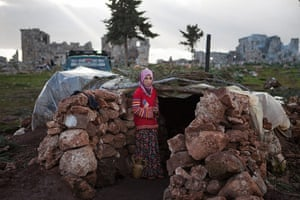 20 Photos: A Syrian girl stands at the entrance of a makeshift home in Serjilla