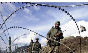 Indian soldiers patrol along a barbed-wire fence in Kashmir