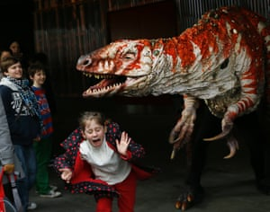 Children react as a carnivorous theropod known as the Australovenator walks through crowds along the Southbank, in London. The dinosaur is one of many that can be visited at the Erth's Dinosaur Petting Zoo, visiting from Australia, the creatures can be touched and fed at the Southbank Centre. Photograph: Kirsty Wigglesworth/AP