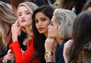 Model and actress Rosie Huntington-Whiteley (L), actress Freida Pinto (C) and singer Rita Ora watch the presentation of the Burberry Prorsum Autumn/Winter 2013 collection during London Fashion Week.