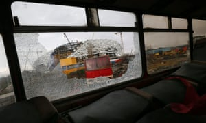 The Olympic stadium for the Sochi 2014 Winter Olympics is seen through the broken window of a scrapped bus in Adler, near Sochi. The complexes and venues at the Black Sea resort are due to be completed by August, according to organizers.