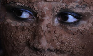 A woman caked in mud takes part in a presentation during the inauguration of the National Meeting of Rural Women in Brazil. The four-day event aims to discuss the issues of violence against women and exploitation of women in rural areas.