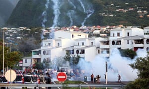 Demonstrators face riot police in the city of Le port, on the French island Reunion, during protests to demand government-subsidised contracts.