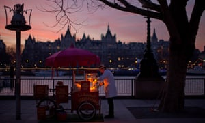 A man tends his popcorn stand at sundown on London's South Bank.