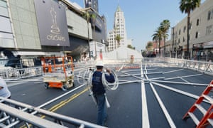 A worker carries building materials on Hollywood Boulevard in preparation for the 85th Academy Awards ceremony. A section of the boulevard in front of the Dolby Theatre will be closed for an entire week as crews build press risers and fan bleachers and roll out the red carpet for the ceremony, which is due to take place on Sunday.