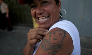 A woman shows a tattoo depicting Hugo Chavez during a celebration at Bolivar square in Caracas, marking the Venezuelan President's return to his country after more than two months of cancer treatment in Cuba.