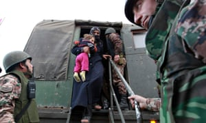 Jordanian soldiers help Syrian refugees disembark from a vehicle after crossing the border from Syria into Jordanian territories, near Mafraq. According to the Jordanian Armed Forces, around 89,000 Syrian refugees fleeing from the violence in their country have crossed the border since the beginning of 2013.