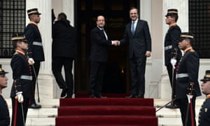 Greek Prime Minister Antonis Samaras and French President Francois Hollande shake hands in Athens at a whistle stop meeting