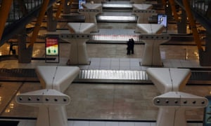 Passengers talk at the empty baggage claim area in Terminal 4 of Madrid's Barajas airport.