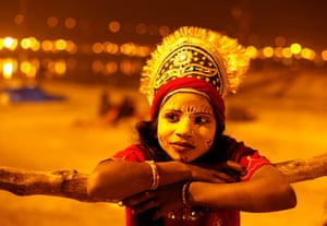 24 hours: A child dressed as Hindu goddess Parvaty, watches a religious procession