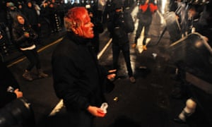 A wounded demonstrator shouts at riot policemen as clashes erupt during a protest against the government in downtown Sofia on February 19, 2013.