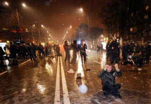 A demonstrator (R) sitting on the floor reacts as clashes erupt between riot policemen and demonstrators during a protest against the government in downtown Sofia on February 19, 2013.