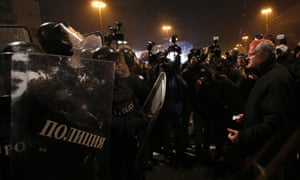 An injured man argues with riot police during a protest against high electricity prices in Sofia February 19, 2013.