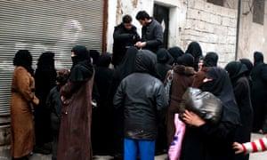 Women queue for food in Aleppo, Syria