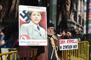 A demonstrator holds up an image of German Chancellor Angela Merkel dressed as a Nazi, while the man holding it has a noose around his neck, during the protest. -