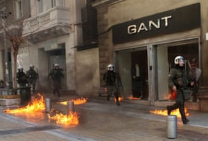Riot police run by closed shops after protesters threw a petrol bomb following an anti-austerity march during a 24-hour strike February 20, 2013.